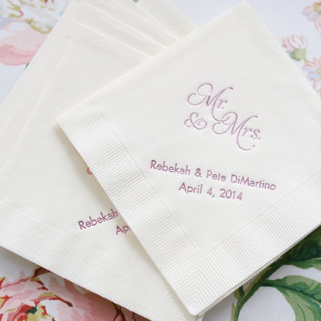 At cocktail hour, guests grabbed champagne and other beverages with these shining purple personalized cocktail napkins from The Knot Shop with the date of the wedding.