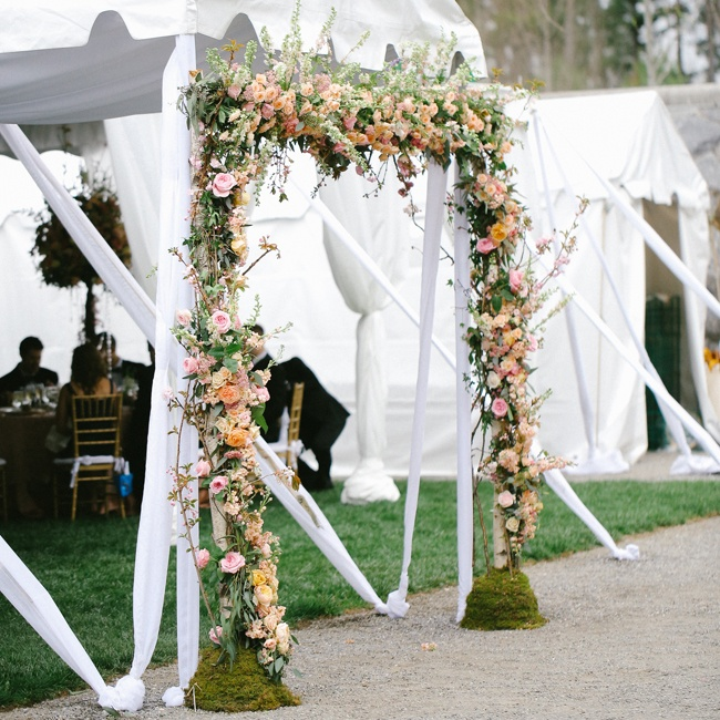 Flowers for the Dream Wedding were provided by American Grown and the  California Cut Flower Commission and designed by Holly Heider Chapple Flowers. The entrance to the tented reception area mirrored the ceremony's floral arch with garlands of roses and peonies lining a frame of birch trees.