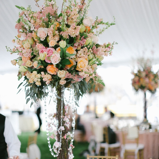 "Statement-making bouquets of roses and snap dragons in peach and blush sat atop tall tree branches draped with crystal, keeping with the ""Enchanted Garden"" theme America chose for the couple. Flowers for the Dream Wedding were provided by American Grown and the California Cut Flower Commission and designed by Holly Heider Chapple Flowers."