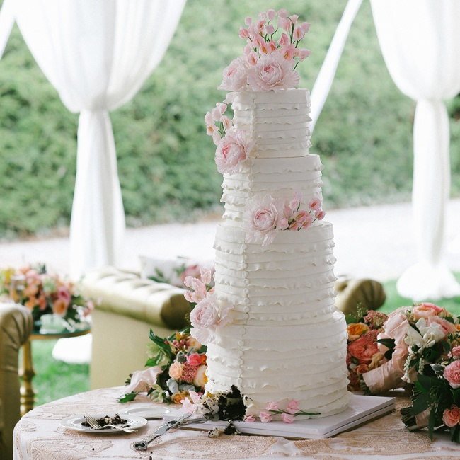 "America chose between four cakes for the Dream Wedding and decided on this white, four-tiered ""Ruffles and Buttons"" themed cake by Cake Alchemy."