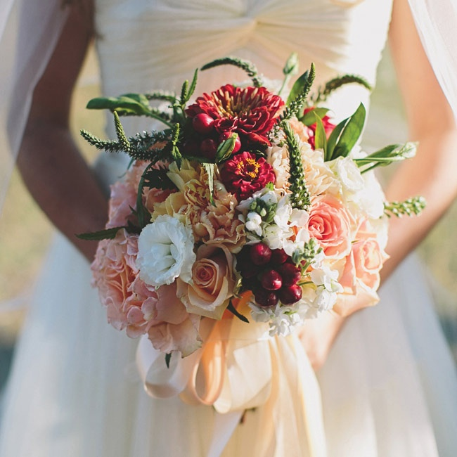 Katie wanted to create a boho chic feel for her bouquet, so her florist put together an eclectic mix of roses, zinnias, lisianthuses, veronica, hypernicum berries and wheat in shades of ivory, peach and deep red.