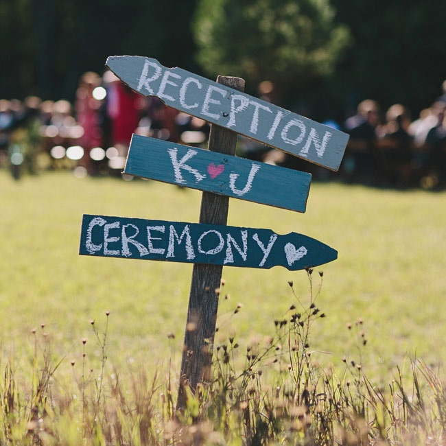 Hand-painted wooden signs directed guests to the ceremony and reception.