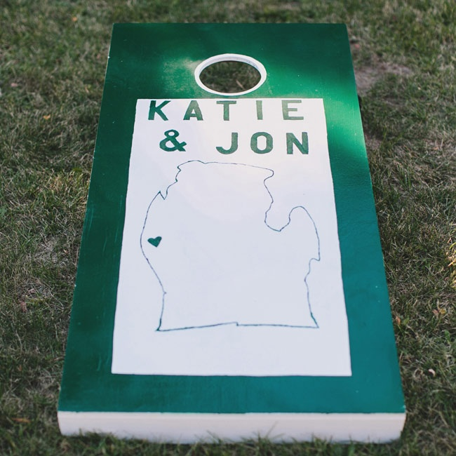 Guests played games like cornhole during the cocktail hour with boards painted with the couple's names and the outline of the state of Michigan.