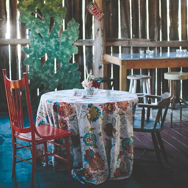 Katie, Jon and their guests came together in the rustic barn for cocktail hour. Bright floral linens covered the tables set with mismatched chairs for a rustic chic look. An acoustic duo provided the music that guests enjoyed while sipping on the couple's signature drinks.