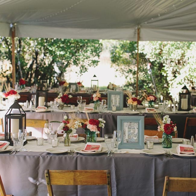 The reception was held under an open air tent. The tables were covered with slate blue cloths and ivory table runners. Bright peach, red and ivory flowers filling blue mason jars and lanterns holding white pillar candles lined the centers of the table.