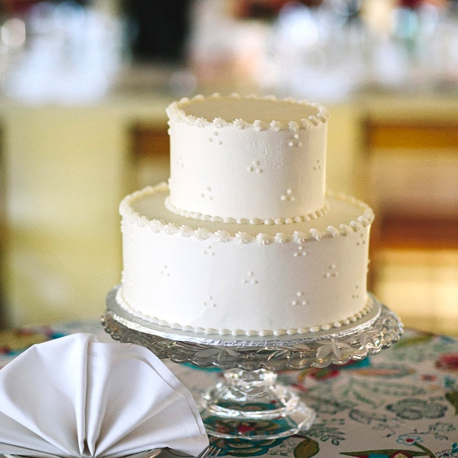 The couple chose a simple two-tier cake with ivory frosting and a sweet swiss dot pattern.