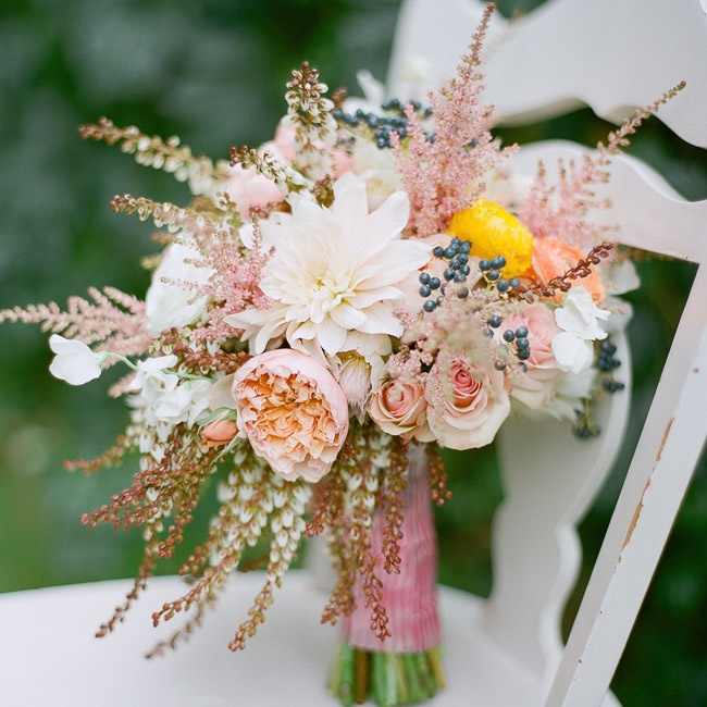The bridal bouquet combined the textured looks of pink astilbe flowers with large dahlias and subtle peach peonies.
