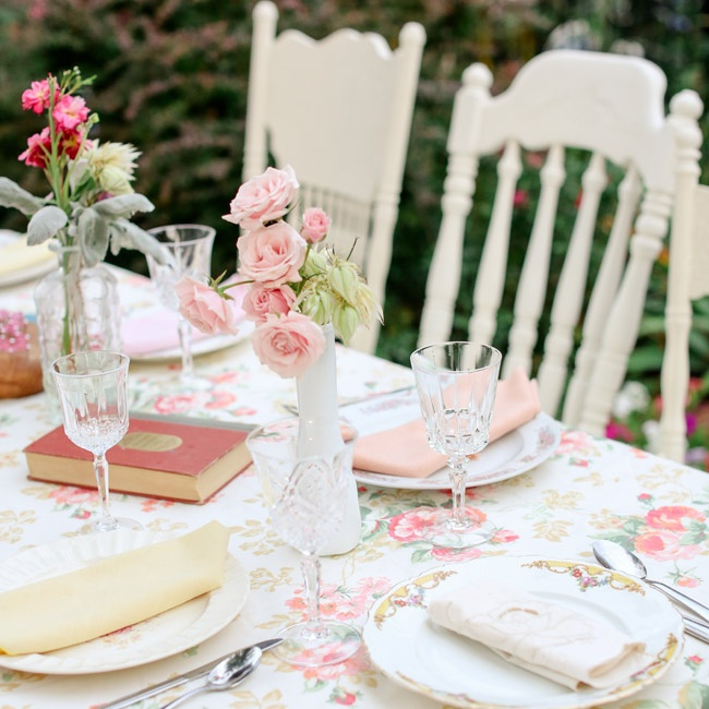 Sweet, small bouquets of roses, vintage books and floral tablecloths made the casual reception into a romantic garden party.
