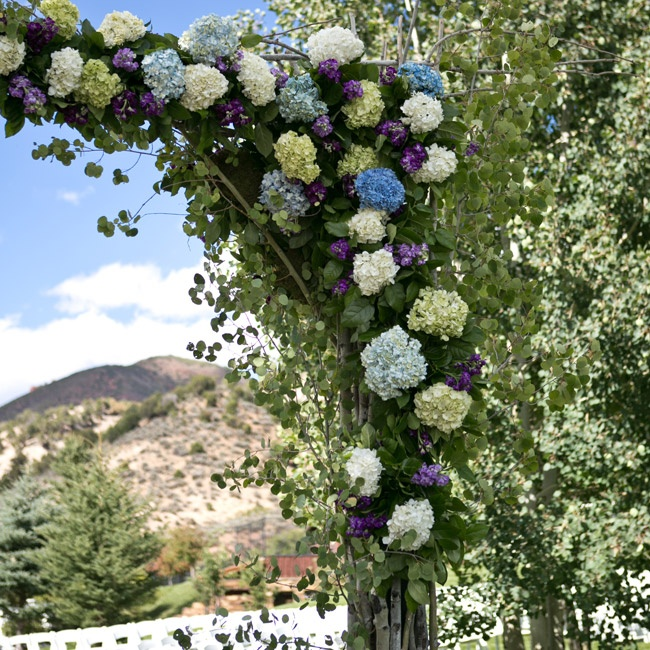 The couple exchanged vows outdoors beneath this arch of blue and white hydrangeas.