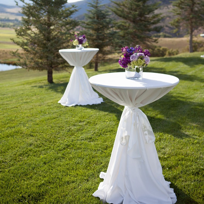 Formal cocktail tables were covered with white linens and set with purple floral centerpieces.