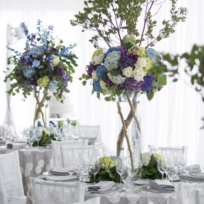 In the reception tent, floral arrangements sat atop tree branches.