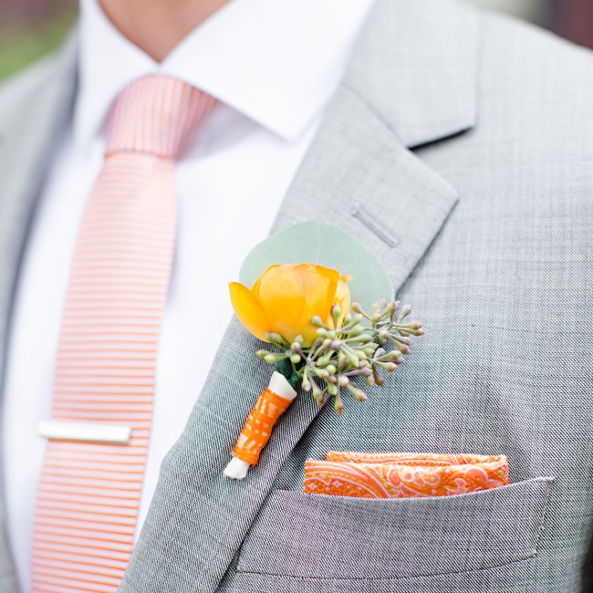 The groom accessorized his light gray suit with a checkered orange tie and a paisley pocket square. He matched the look with a mustard yellow floral boutonniere.