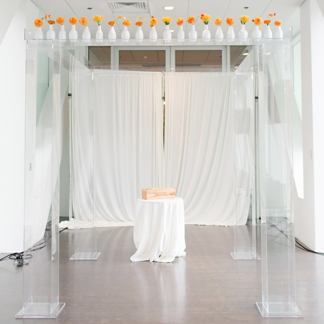 The couple exchanged vows beneath a lucite frame topped with orange flowers in white vases for a very modern look.