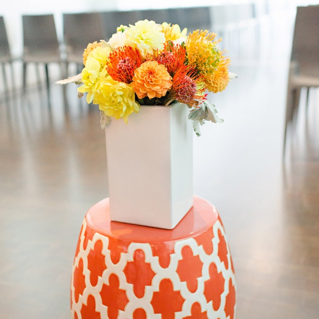 Decorations at the ceremony were modern and full of pops of orange, white and yellow. White box vases were filled with orange dahlias and yellow and red pincushion proteas.