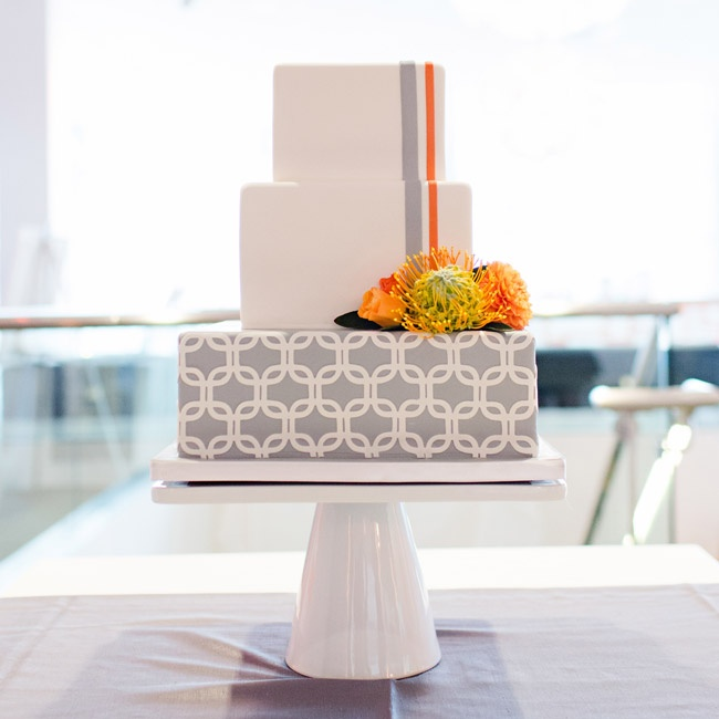 The cake was printed with a geometric gray pattern and accented with orange and yellow pincushion proteas.