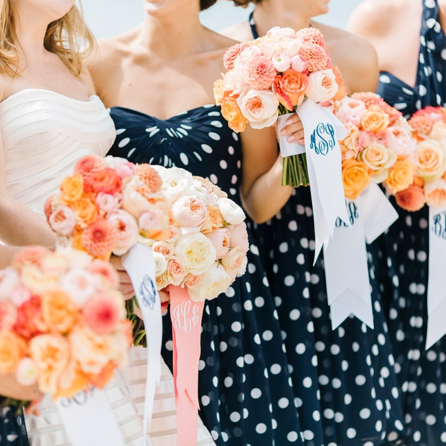 The bridesmaids carried bright bouquet of peach, pink and ivory dahlias, roses, peonies and ranunculuses tied with white ribbons monogrammed with their initials.