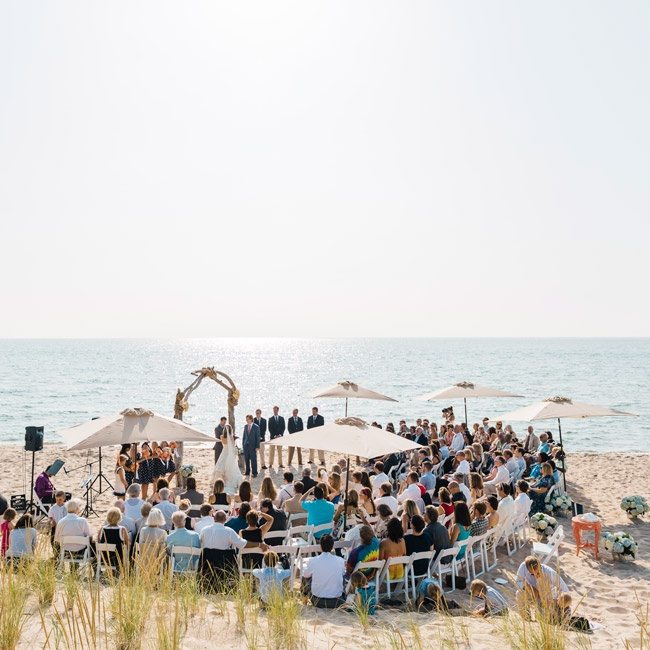 The couple held the ceremony right on the beach of Lake Michigan at Jamie's parents home. They exchanged vows in front of a unique driftwood arch, which they made from pieces of wood that they had collected from the beach over the summer.Large beach umbrellas were scattered among the aisles to provide shade from the summer sun.