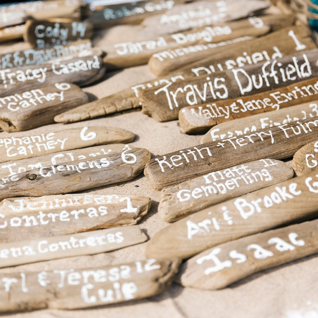 Jamie's mother spent months collecting driftwood, which they later bleached and then hand calligraphed with the name and seating assignment of each guest.