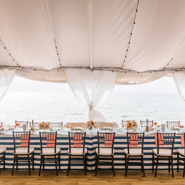The newlyweds and bridal party sat at a long table set with navy and white striped linens and bright coral napkins.