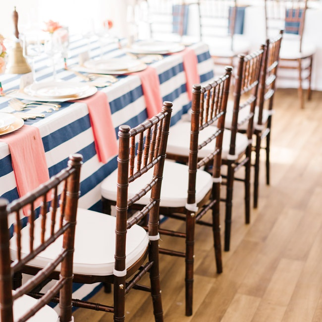 Dark brown chiavari chairs paired perfectly with the navy, white and coral color scheme, adding a sophisticated touch.