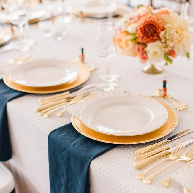 Guests sat along long tables set with white linens embroidered with a Swiss dot design and topped with navy napkins. Gold chargers and silverware brought an added elegance to the tablescapes. Jamie loves a bit of spice, so mini bottles of Tabasco sauce were placed at each place setting.