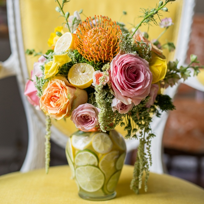 Lemon halves, pincushion flowers and hanging moss give a modern textured look to the centerpieces. Vases are filled with lemon and lime slices to tie into the citrus theme.