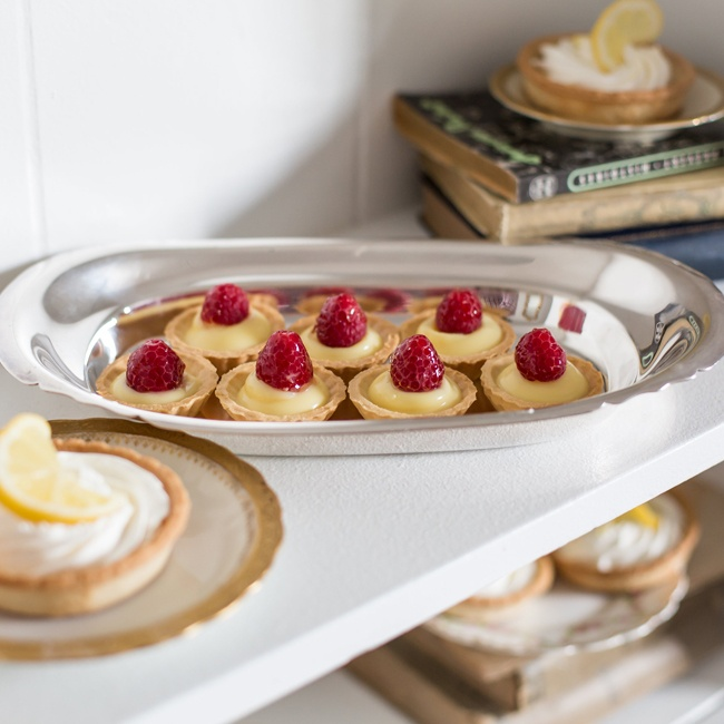 Miniature lemon tarts, each with a juicy raspberry on top, are the perfect mix of sweet and tart.