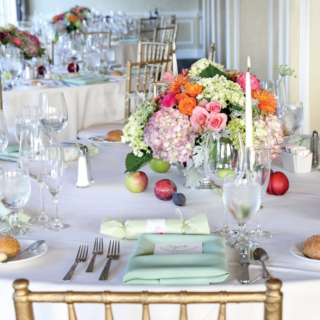 "The lush centerpieces of garden roses, dahlias and hydrangeas referenced the colors in the watercolor pattern throughout the whimsical invitation suite. Seasonal end-of-summer fruits in bright colors (including plums, apples and peaches) surrounded the floral arrangements. ""The first time I walked into the reception room, the late afternoon sun was ..."