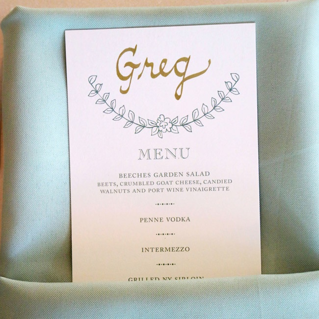 Classic white table clothes with sage green napkins housed menus which the bride calligraphed in gold ink with each guest's name.
