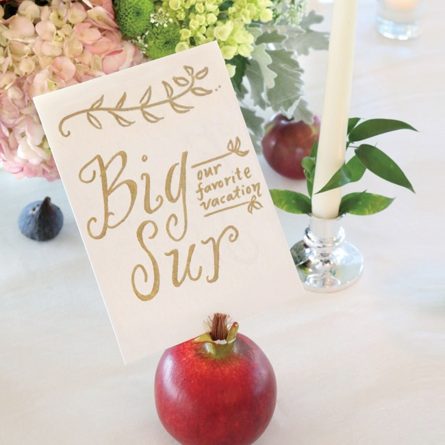 The bride designed each table name as a different location significant to the couple and displayed the signs in a pomegranate.