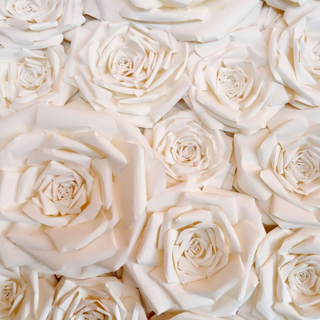 A whimsical paper flower wall with big garden roses served as a backdrop for the wedding cakes and created a focal point for the reception space.
