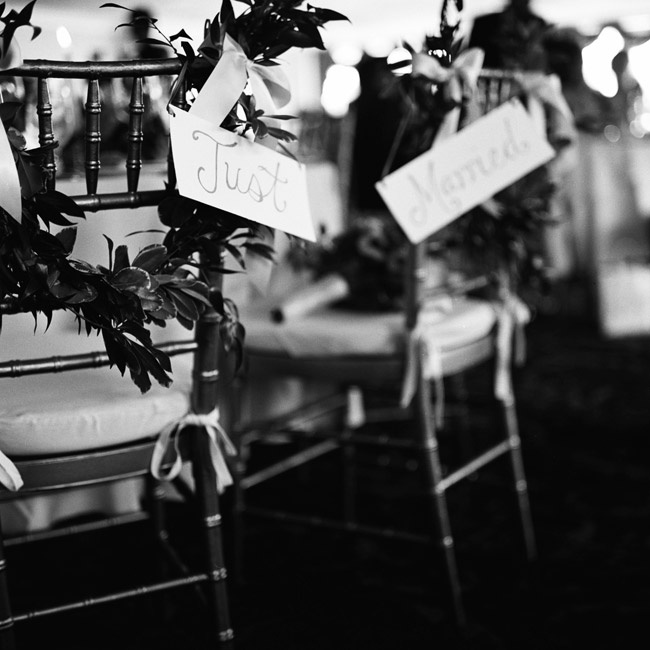 "Ivory and gold ""just married"" signs hung from the newlyweds' chairs along with lush green garlands."