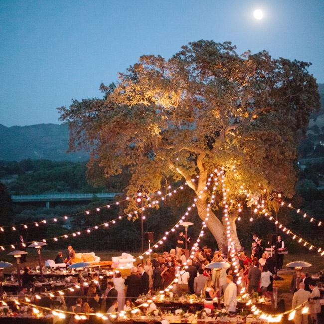 "As the night wore on, globe lights strung from an oak tree cast a warm glow on the reception. ""While our guests danced, a super-moon rose in the evening sky,"" recalls Rachel. ""We couldn't have arranged a more perfect backdrop!"""