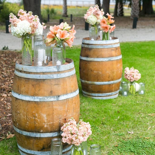 Wine barrels topped with bright peach flowers in dotted mason jars gave a cheerful, rustic air to the ceremony decor.