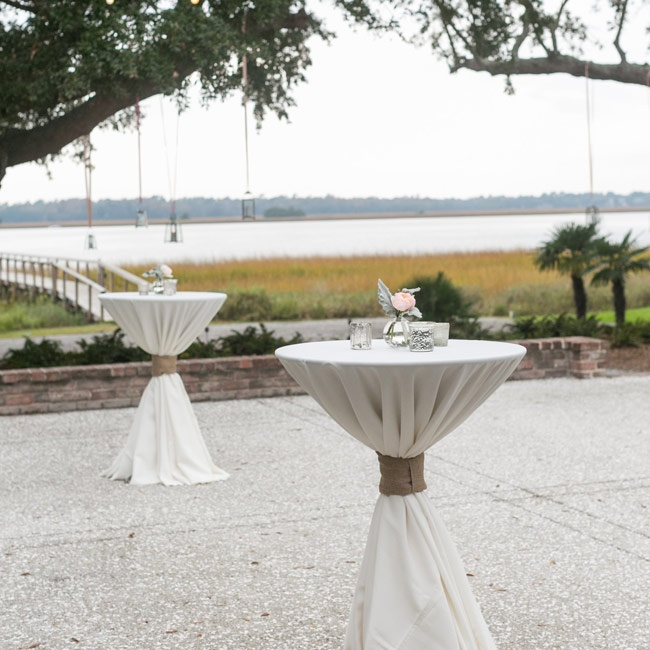 The cocktail hour was held outside where guests could enjoy panoramic views of the river while sipping on drinks. The cocktail tables were covered in neutral linens. Silver mercury glass votive candles and bud vases filled with pink roses and lamb's ear topped each table.