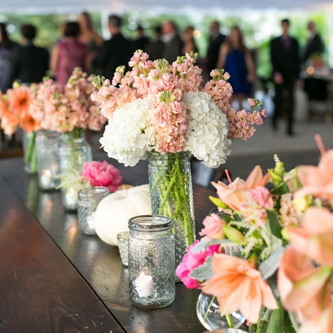 Dotted glass added a unique twist to the mason jar vases, which were filled with candles and pastel flowers.