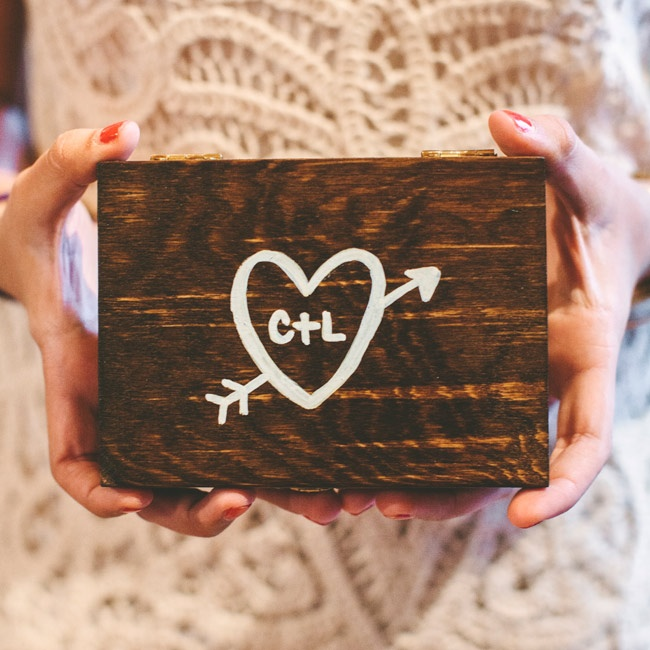 Decorations at the ceremony and reception included this DIY distressed wooden box with the couple's initials painted on.