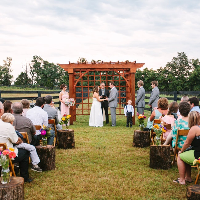 The ceremony aisle was lined with tree stumps topped with floral arrangements.