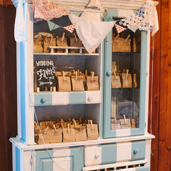 Guests grabbed their wedding favors from this blue and white striped, repurposed cabinet.