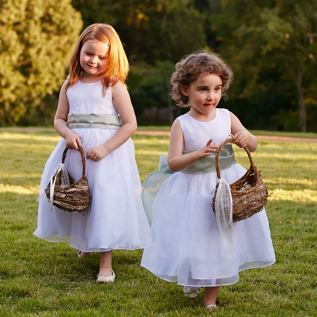 The flower girls wore white dresses with full organza skirts and a sage colored bow at the waist. They carried rustic wicker and tree bark baskets tied with white ribbon and lace.