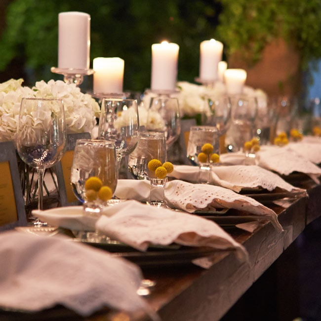 Long farm tables were given a rustic, romantic air with white pillar candles on clear candle sticks, bunches of white hydrangeas and white eyelet napkins with craspedia accented napkin holders.