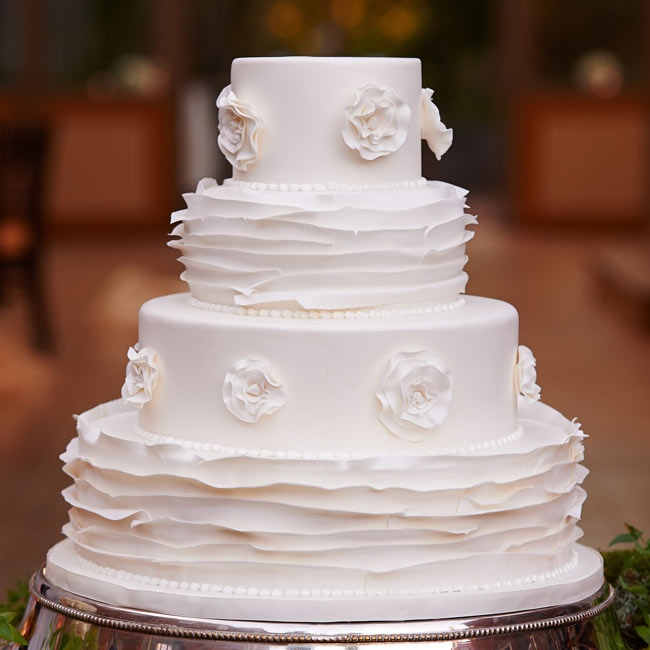 The cake was a white fondant four-tiered cake with alternating rosette and ruffle patterns.