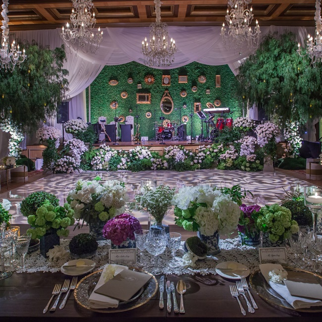 """Leslie and Ryan hosted a sophisticated ballroom reception filled with blue-and-white Chinoiserie vases and lush greenery. """"Each table had simple, but elegant candle light and I requested that the center pieces for the tables be kept low so each guest could easily converse as well as as well as easily look up to the stage for the speeches,"""" says Les ..."""