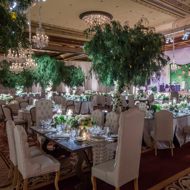 """I loved how the romantic theme was played out in the space with four weeping willow trees that were punctuated by flowers that climbed up the trunks of the trees,"" describes Leslie. ""Crystal chandeliers were brought in and placed above the dance floor to draw the eye into the center, really enhancing the intimate and romantic feel of the room."""