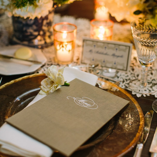 """Places were set with the a sophisticated menu for the seated dinner with the card itself held in a taupe rectangular card also made of heavy card stock that retained the white menu by the corners with fabric that folded over. """"When you flipped the card over, embossed in silver with a decorative type read 'Menu' and I took a bunch of extra menus hom ..."""