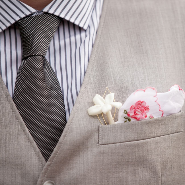 The groom wore a striped shirt with a charcoal tie and light gray vest with an embroidered handkerchief as a pocket square.