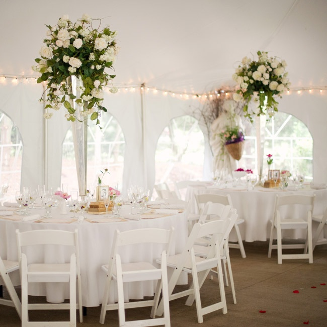 The reception took place in a white tent with windows and featured large white rose centerpieces.