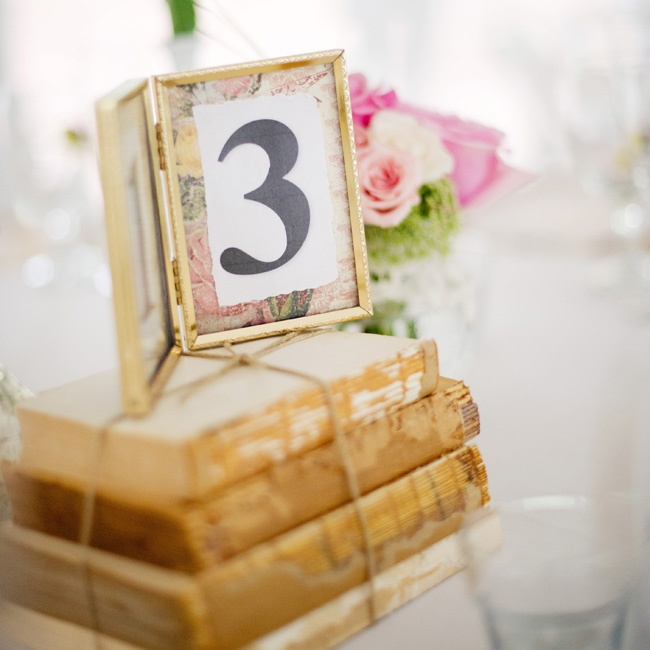 decorations of vintage books and floral table numbers in vintage photo frames were placed on the reception tables.