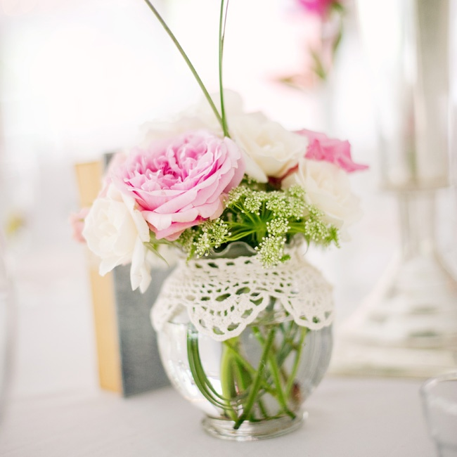 Pink and white roses filled small, round, glass vases at the reception.