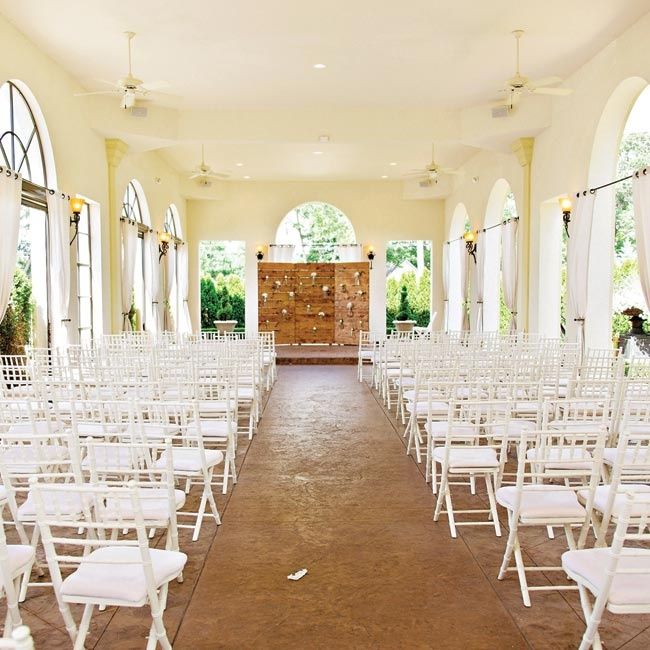 The ceremony was held in the open air chapel at Crystal Gardens. The couple liked the simplicity of the space and the views of the surrounding of lush gardens. Lauren and Josh added a simple, handmade backdrop, a paneled wood structure with hanging jars filled with hydrangeas, ranunculuses and greenery.
